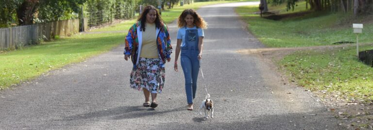 Mother and daughter walk dog