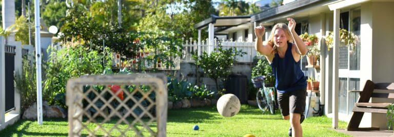 Teenage boy throws football into crate