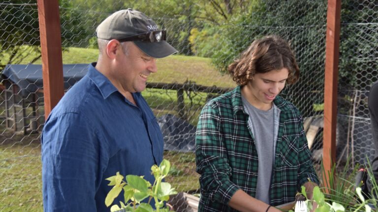 Man and son plant herbs in garden