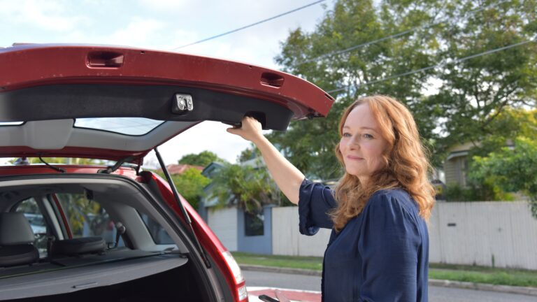 Woman smiles as she closes boot of car