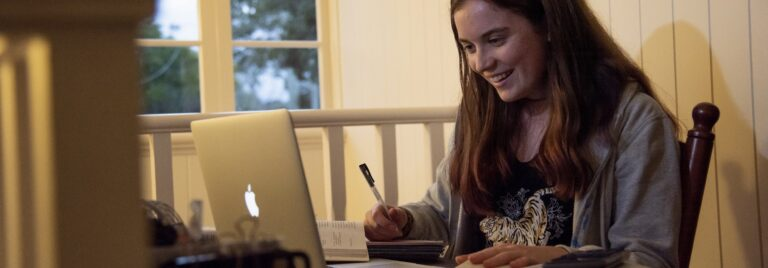 Girl smiles while studying with textbooks and laptop