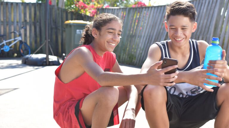 Boy holds phone up to friend on basketball court.