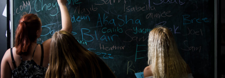 Three girls write on chalk board.