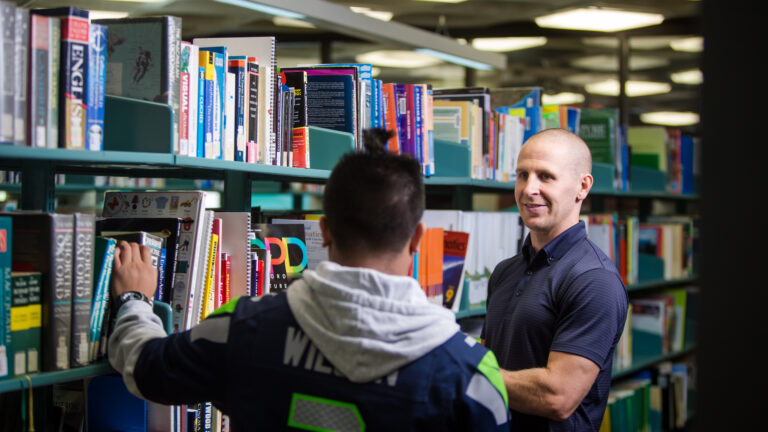 Student and teacher choose a book from library shelf