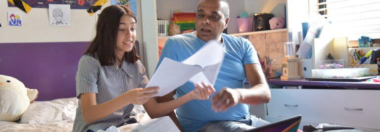 Father sits with daughter and helps with homework